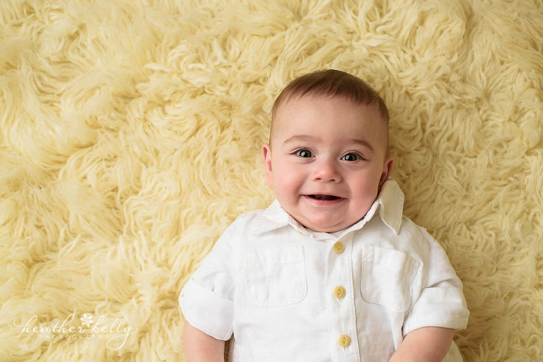 smiling 6 month boy on flokati rug