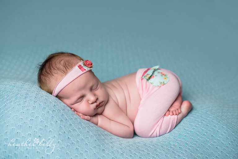 newborn girl with pink pants on blue blanket
