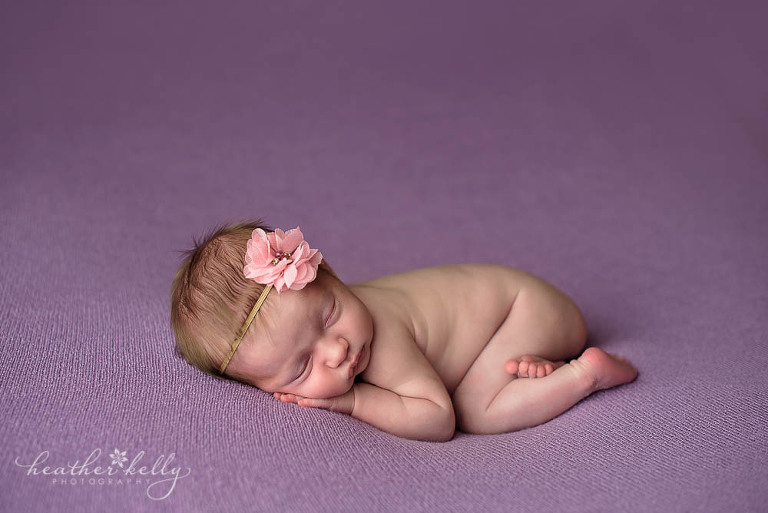 naked newborn girl on lavender blanket with pink headband