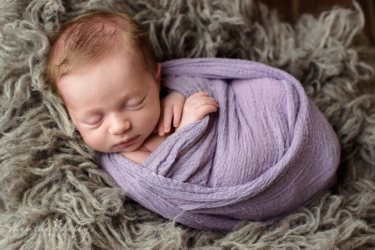 baby girl with lavender wrap on gray flokati