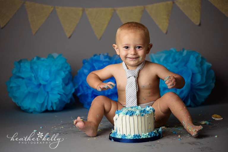 gray background cake smash with white and blue cake