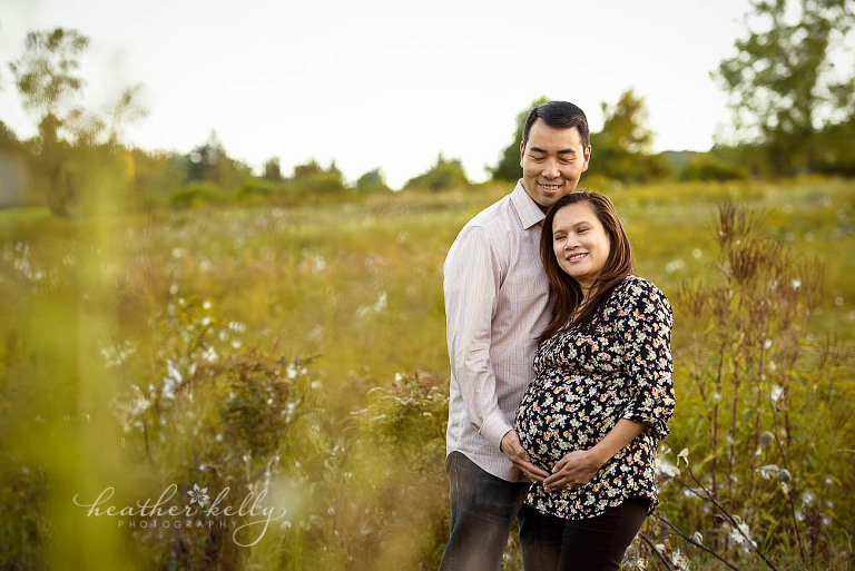 maternity photo with mom and dad in field