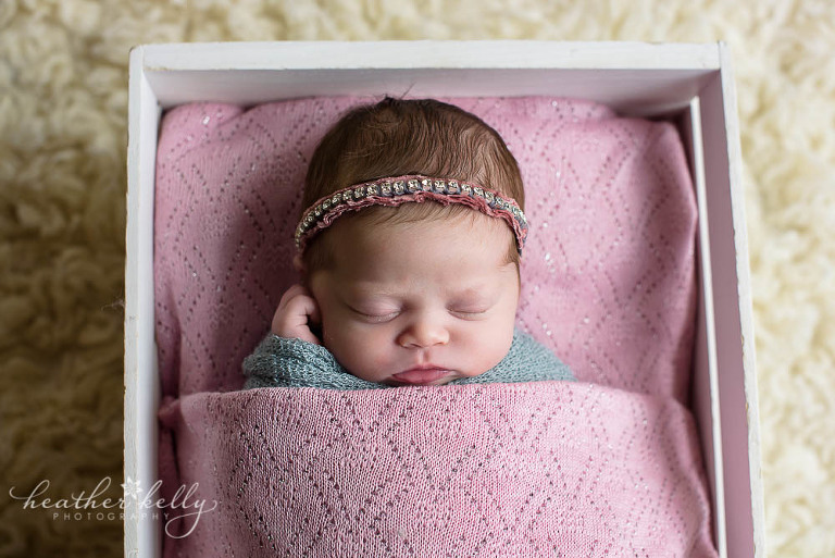 baby girl wrapped and tucked in crate with blanket newborn blog circle