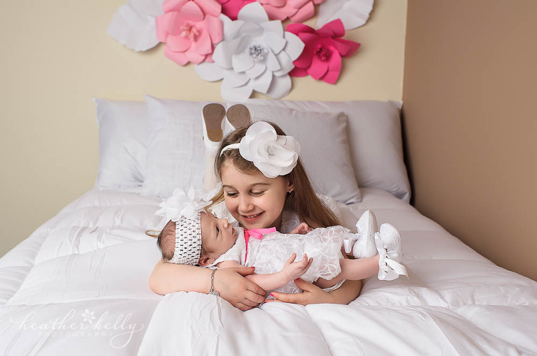 ct newborn photographer | big sister hold baby girl on bed photo | newtown newborn photos
